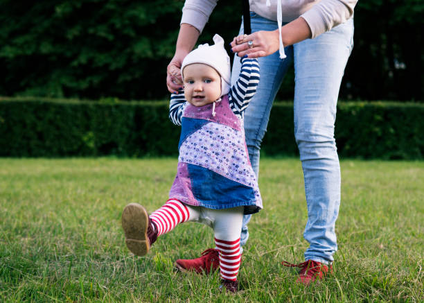 A baby is making the first steps stock photo