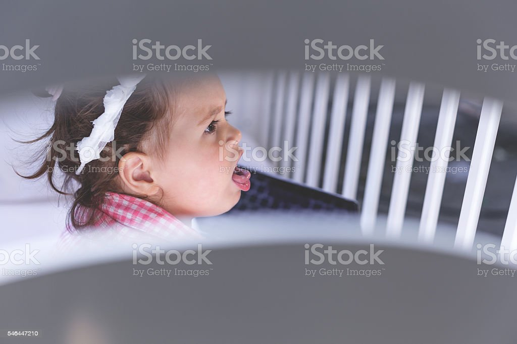 baby is sitting in a crib and coughing stock photo