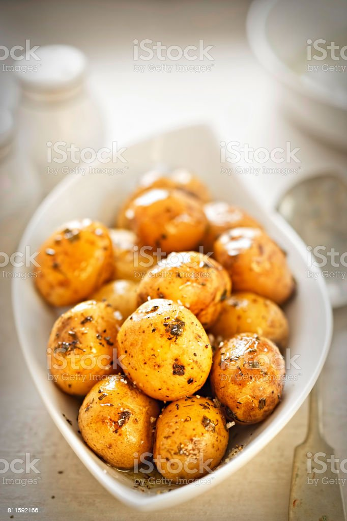 Baby jacket potatoes with herb and garlic oil dressing stock photo