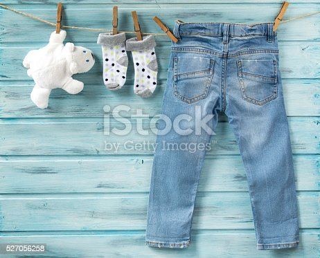 istock Baby jeans, socks and white toy bear on a clothesline 527056258