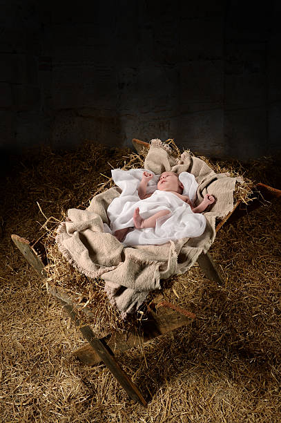 Baby Jesus on a Manger Baby Jesus on a manger inside old dark stable trough stock pictures, royalty-free photos & images