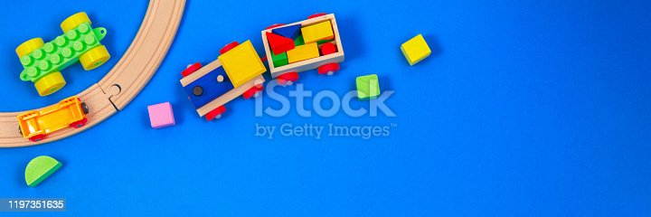 Wooden toy train with colorful blocks on blue background. Top view, flat lay