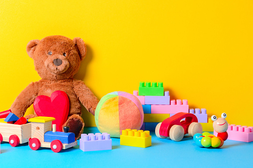 Baby kid toys collection on blue and yellow background.
