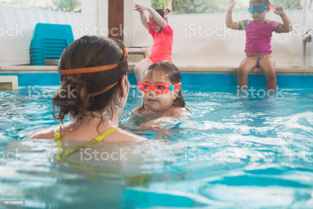 Toddler and baby kids on a swimming lesson at indoor swimming pool.