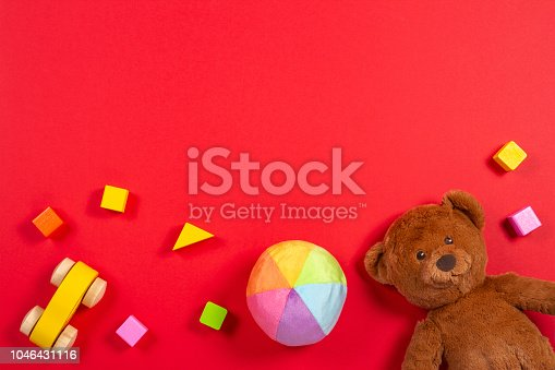 Baby kids toys background. Teddy bear, wooden car, colorful bricks on red color background