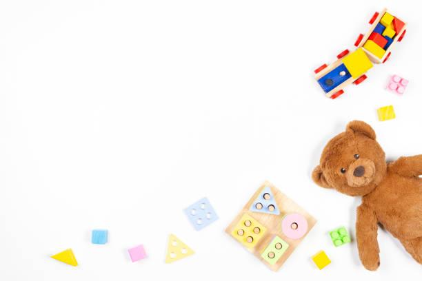 Baby Kinder Spielzeug Hintergrund. Hölzerne pädagogische geometrische Stapelblöcke Form Farbe Erkennung Puzzle Spielzeug, Holzzug, Teddybär und bunte Blöcke auf weißem Hintergrund. Ansicht von oben, flach liegend – Foto