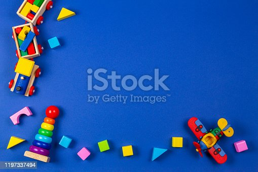 Baby kids toys background. Wooden educational natural toys on navy blue background. Top view