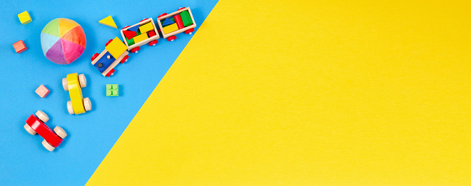 Baby kids toys banner background. Wooden train, toy car, colorful blocks on blue and yellow background. Top view, flat lay