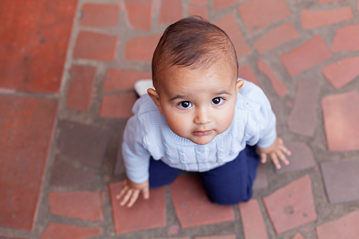 Latino boy from Bogotá Colombia, one year old, looking at the camera in a portrait while kneeling in his new home