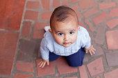 istock Baby kneeling on the floor looking up in a portrait 1285464626