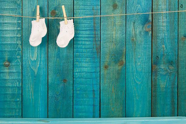 tejido de bebé lana calcetines en color turquesa primako sobre fondo de madera - baby shower fotografías e imágenes de stock