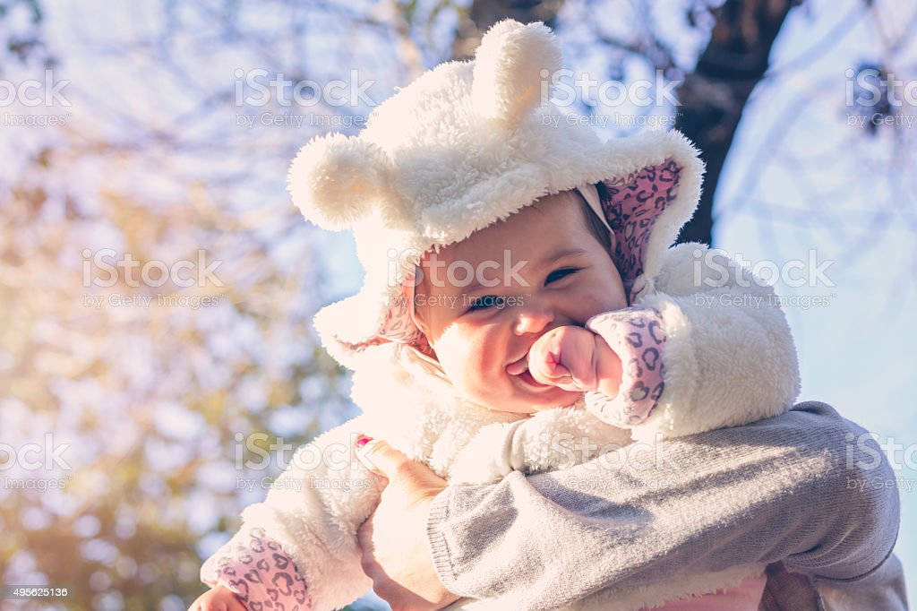 baby laughing in her mother's embrace stock photo