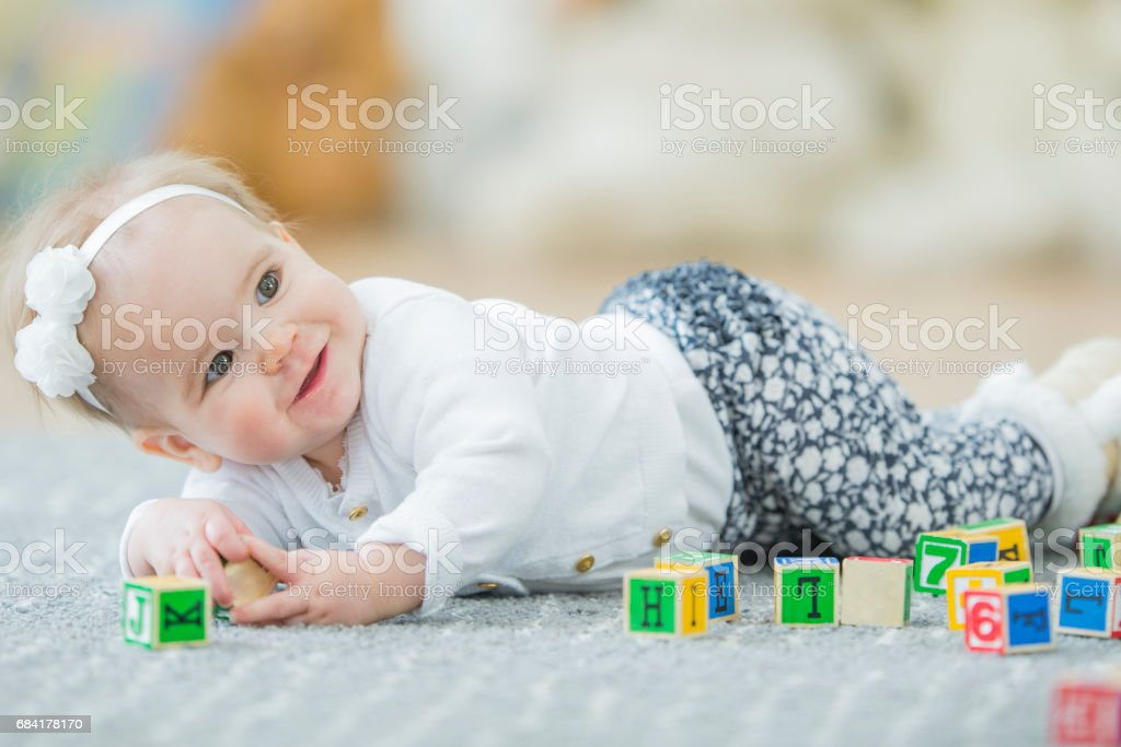 Baby Laying on Carpet Playing with Toy Blocks royalty-free stock photo