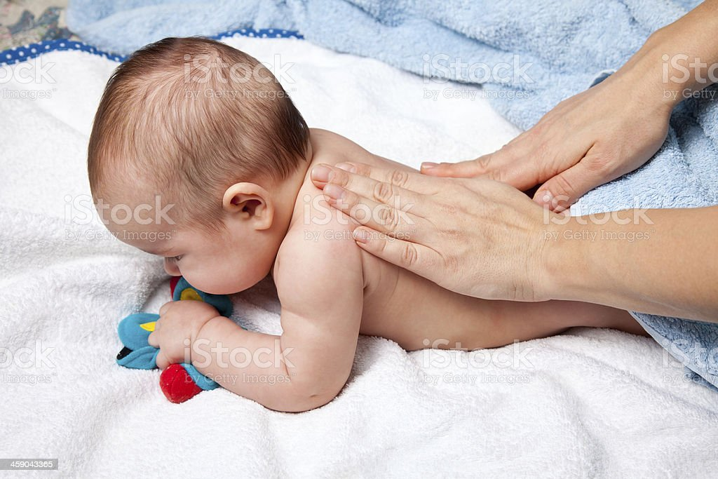 Baby laying on towels getting a back massage stock photo