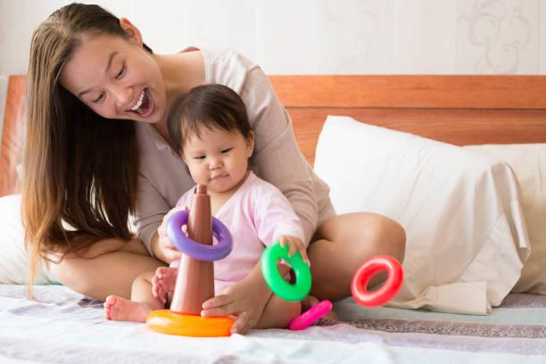 寶寶學習協調技能同時鋪設和一個快樂的自豪的母親看著她的孩子與歡樂合唱團 》圖像檔