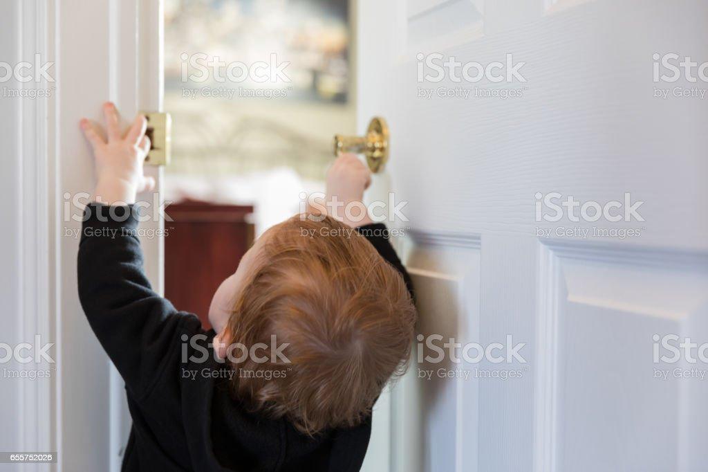 Baby lernen, eine Tür zu öffnen – Foto