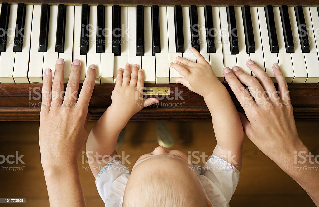 Baby learning to play piano with mother stock photo