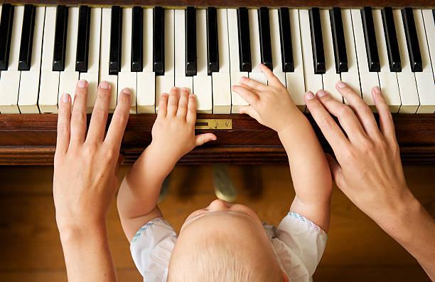 baby lernen zu spielen klavier mit mutter - lautbildungsspiele stock-fotos und bilder