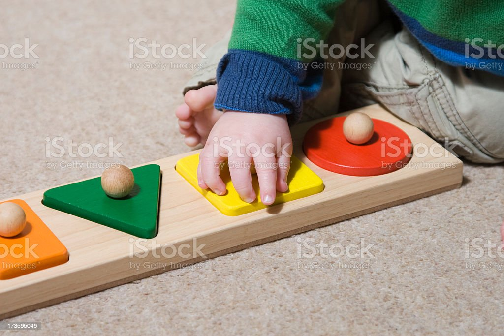 Baby learning to play using large wooden puzzle pieces stock photo