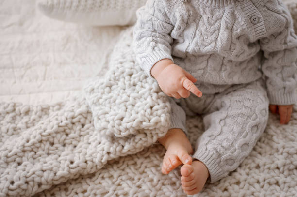Baby Legs in Gray Cable Knit Romper Baby on a bed showing legs, arms, and bare feet, wearing a gray cable knit romper baby clothing stock pictures, royalty-free photos & images