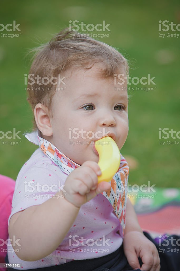 Baby, less than a year old   playing with  toy banana stock photo