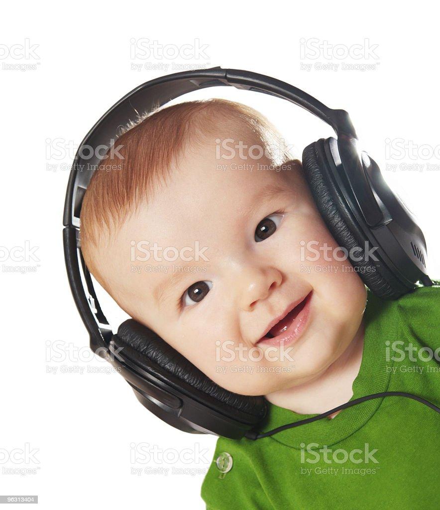 Baby listening to music in headphones - Royaltyfri 0-11 månader Bildbanksbilder