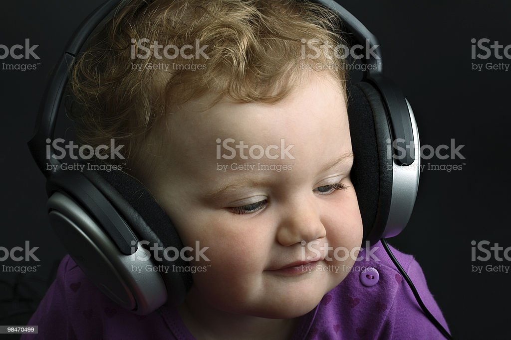 Baby listening to music with huge headphones on black background royalty-free stock photo