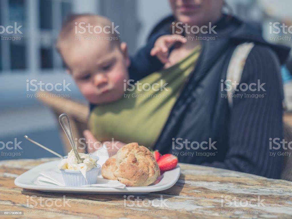 Baby looking at cream tea stock photo
