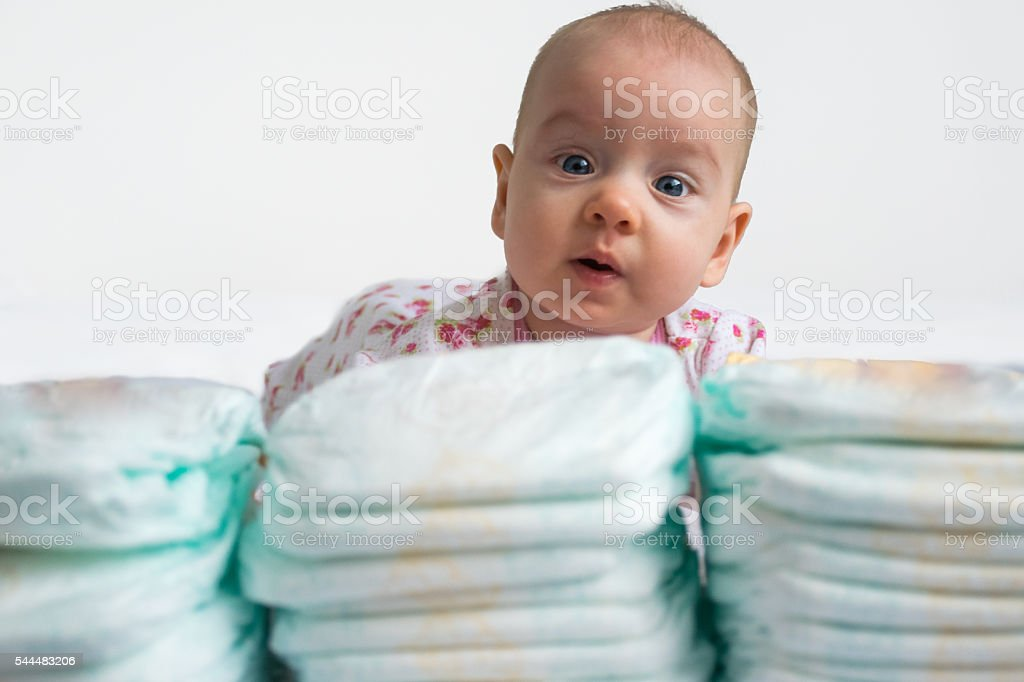 Baby looking over stack of diapers 1 v 2 stock photo