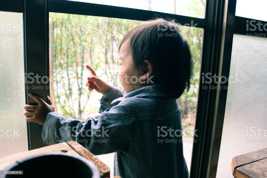 A japanese baby is looking through window