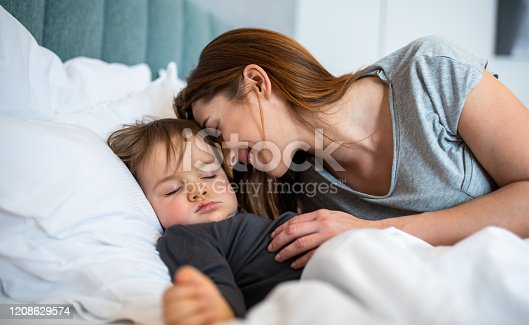 Baby boy lovingly sleeps and cuddles with his own mother.