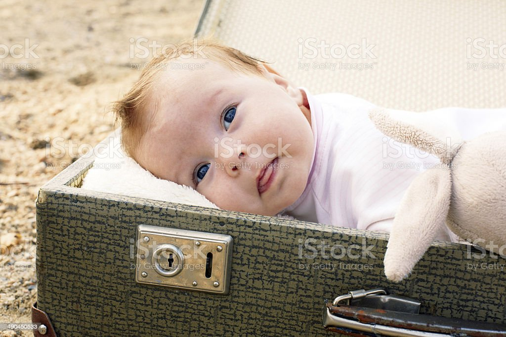 Baby lying in a suitcase stock photo
