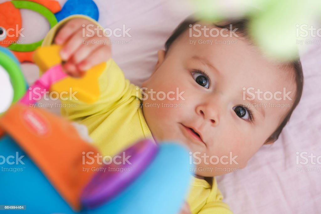 Baby lying in his crib staring at camera surpised stock photo