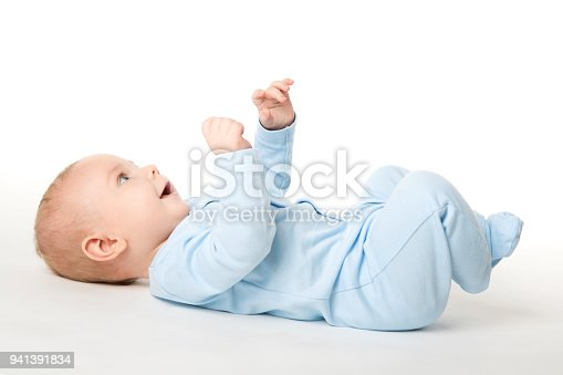 istock Baby Lying on Back, Happy Infant Kid Dressed in Blue Bodysuit, Child on White 941391834