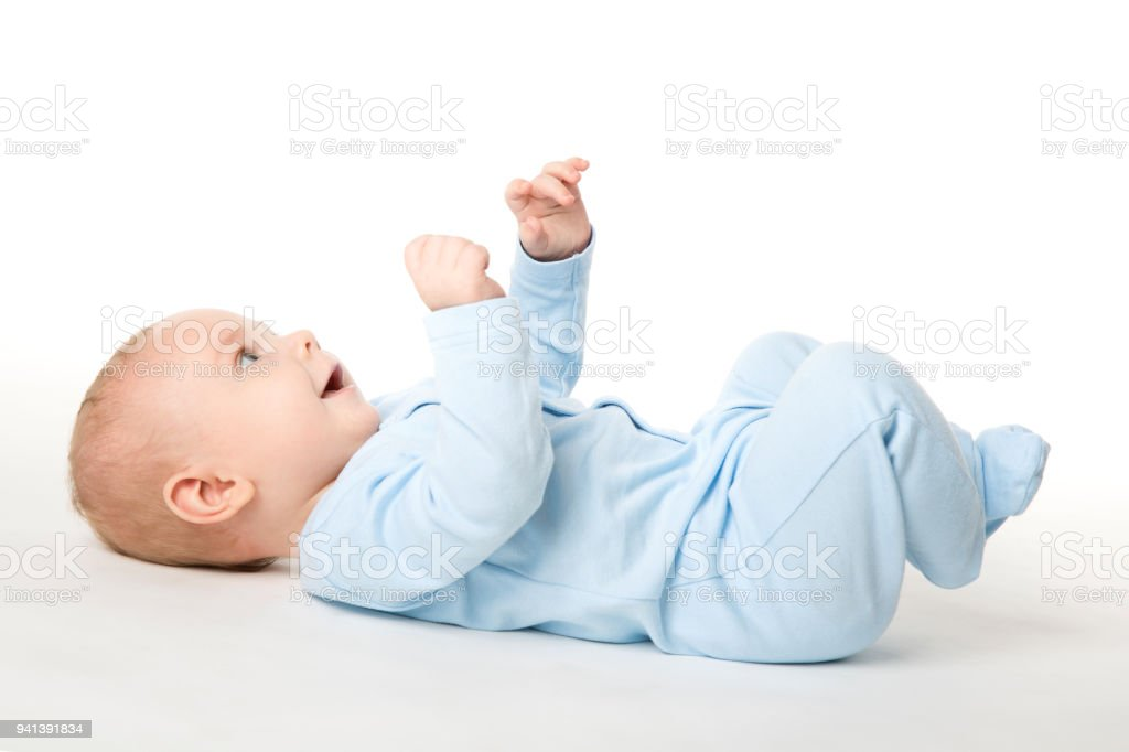 Baby Lying on Back, Happy Infant Kid Dressed in Blue Bodysuit, Child on White stock photo