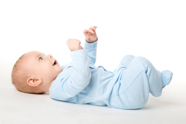 Baby Lying on Back, Happy Infant Kid Dressed in Blue Bodysuit, Child on White Baby Lying on Back, Happy Infant Kid Dressed in Blue Bodysuit, Beautiful Child Lie over White background looking up lying on back stock pictures, royalty-free photos & images