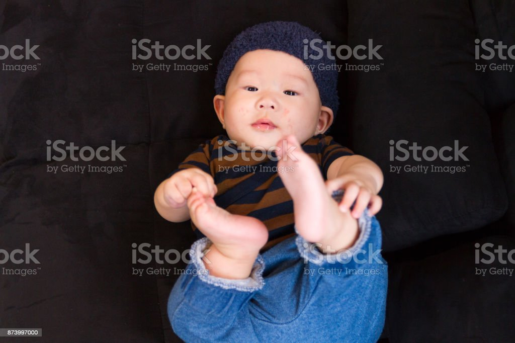baby lying on black sofa stock photo