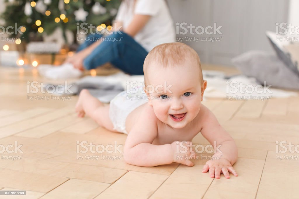 Smiling naked baby lying on floor and looking at camera on blurred...