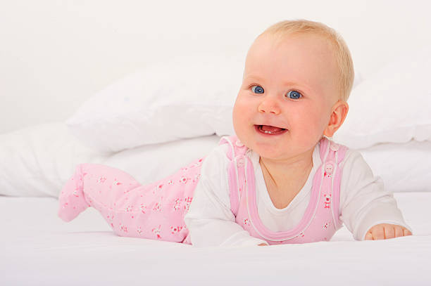 Baby lying on her stomach smiling stock photo