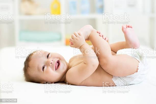 Baby Liegend Weißen Bett Und Halte Die Beine Stockfoto und mehr Bilder von Baby