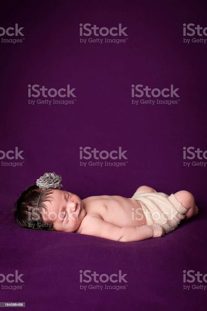 Baby Lying Peacefully on Purple Background With Copy Space royalty-free stock photo
