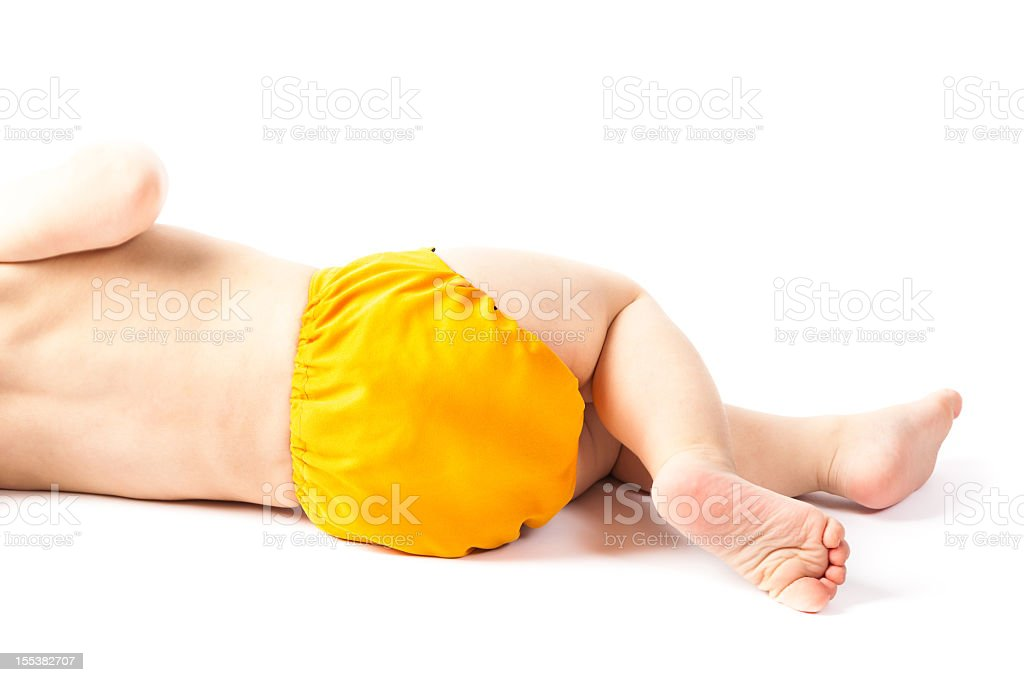Baby lying sideways with yellow cloth diaper on white background royalty-free stock photo