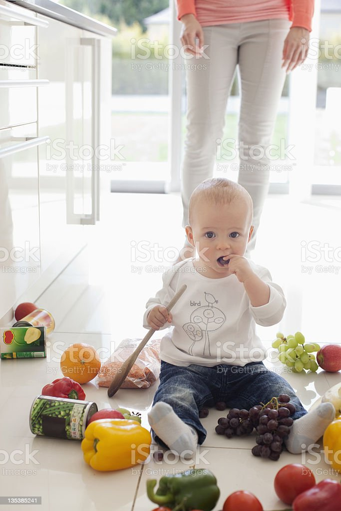 Baby making mess on floor with food stock photo
