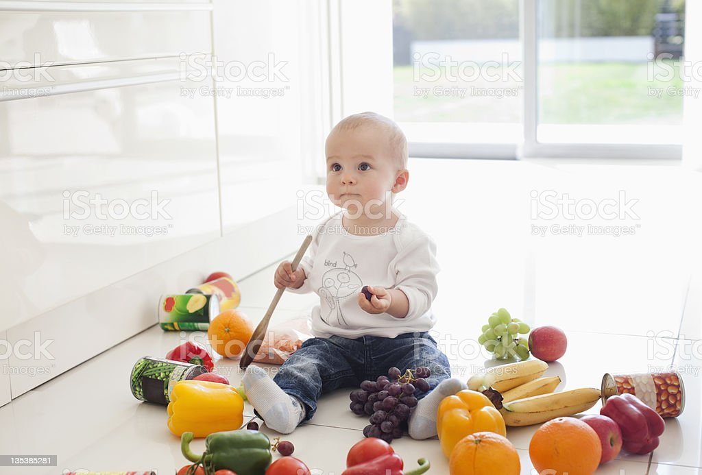 Baby making mess on floor with food royalty-free stock photo