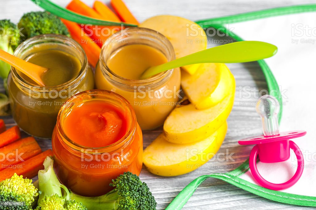 baby mashed with spoon in glass jar on wooden background - foto de stock