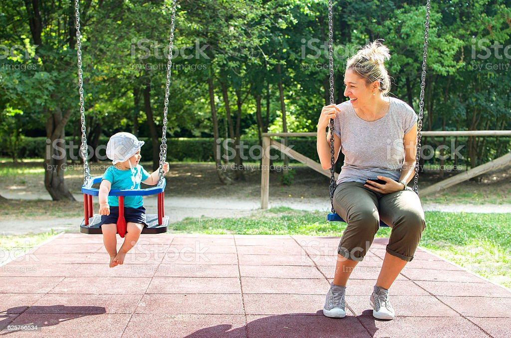 baby mother swing playground looking each other stock photo