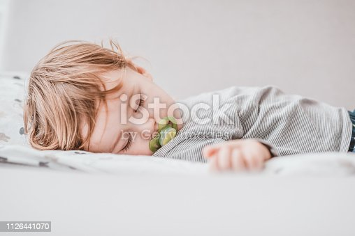 Photo of One year old baby boy sleeping during the day. Baby sleeping with open arms and with pacifier. Daytime sleep of the child.