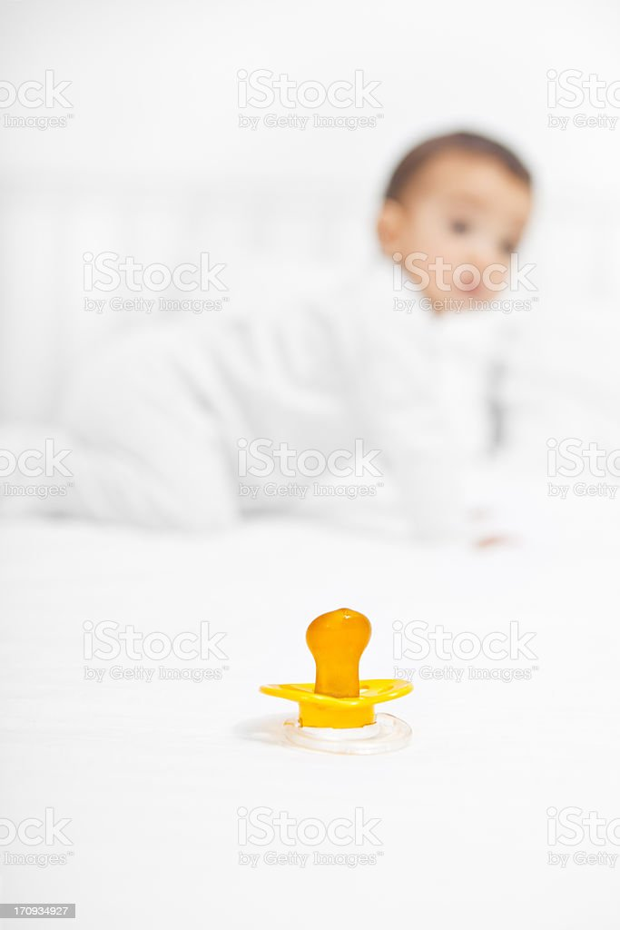 Baby on bed looking for pacifier royalty-free stock photo