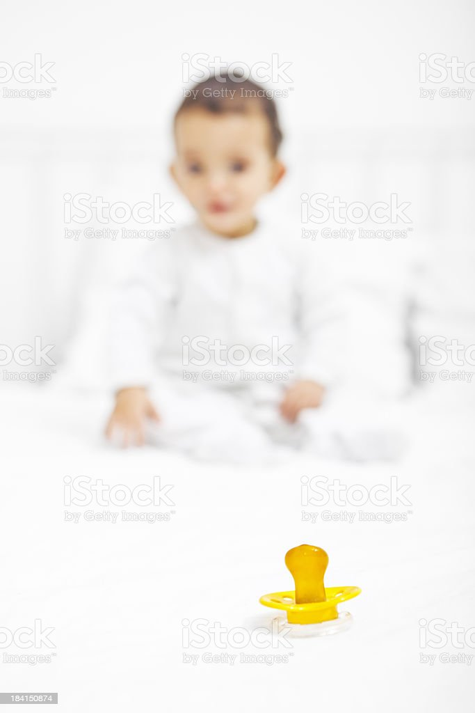 Baby on bed wanting his pacifier royalty-free stock photo