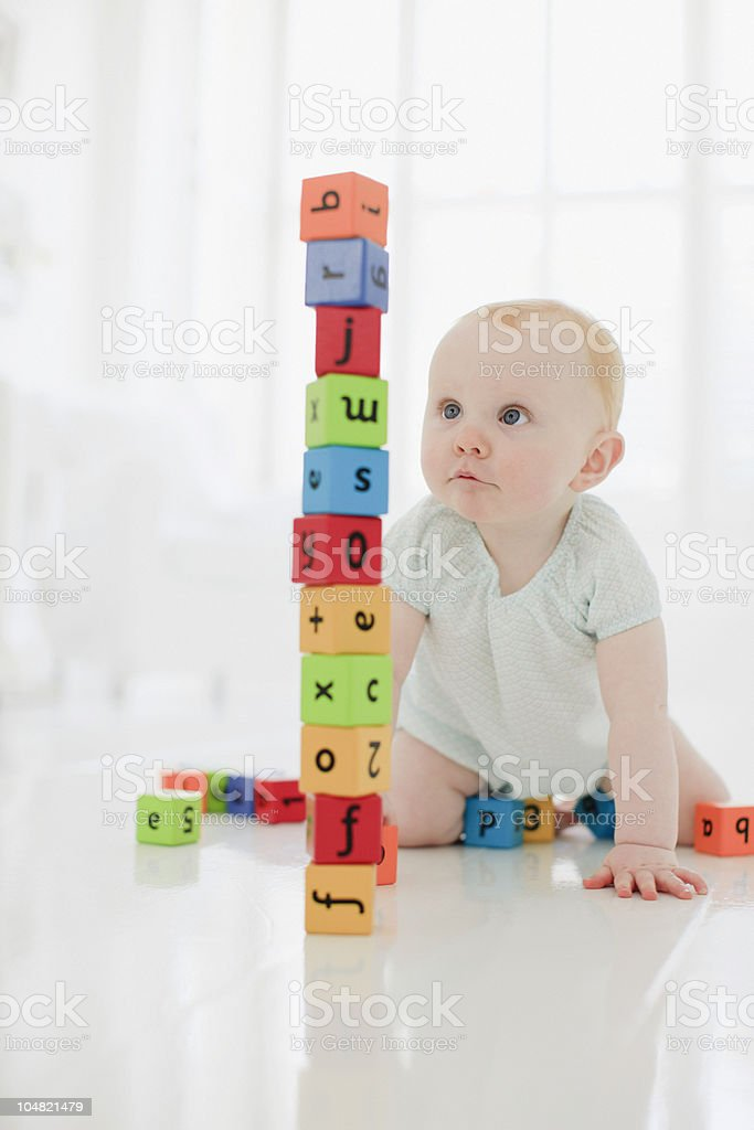 Baby on floor looking at stacked wood blocks royalty-free stock photo
